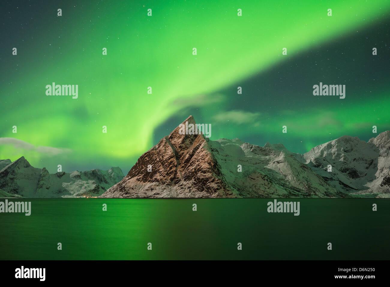 Aurora Borealis - Northern Lights fill sky over Olstind mountain peak and reflect in fjord, Toppøya, Lofoten - Stock Image