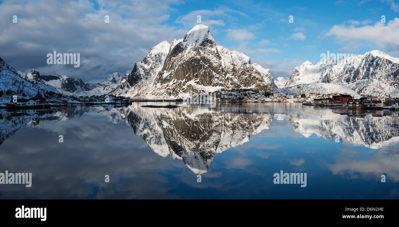 Snow covered Olstind mountain peak rising above Reine, Moskenesøy, Lofoten Islands, Norway Stock Photo