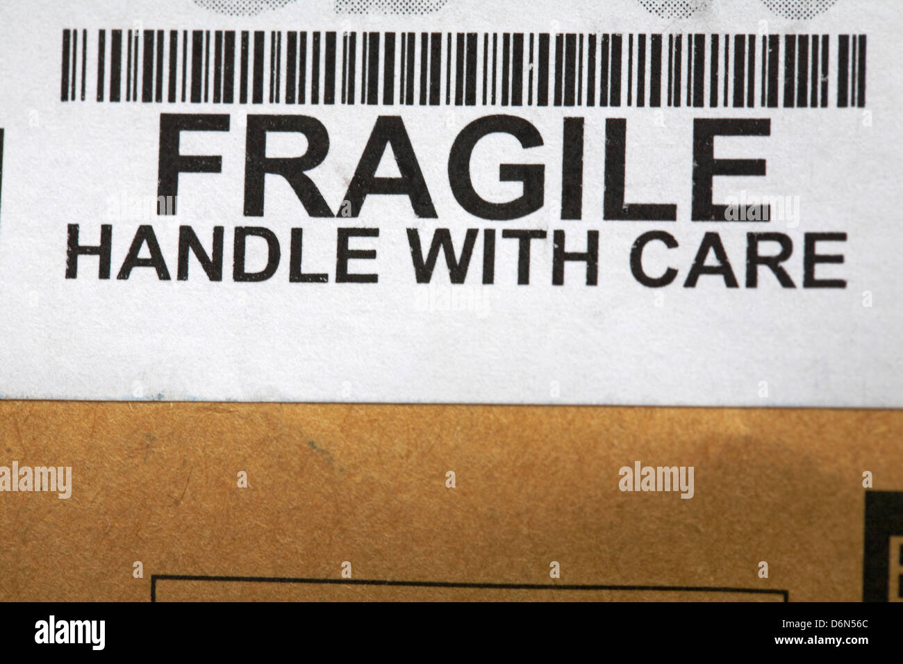 fragile handle with care sticker and barcode on package - Stock Image