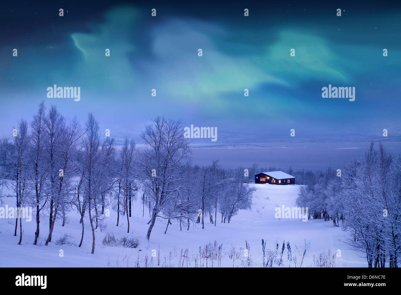 Log cabin at Winter with Northern lights, trees and snow. - Stock Image