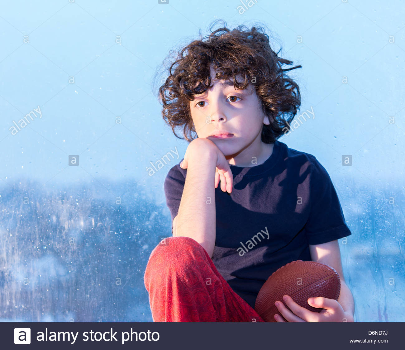 Young Hispanic child sitting in a window waiting for the rain to clear to go and play outside his house - Stock Image