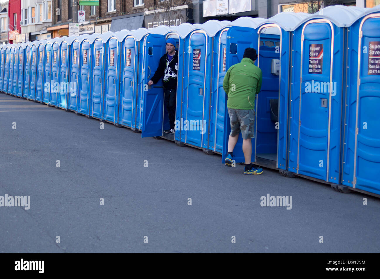 One Person Enters A Portable Toilet While Another Exits A Portable Toilet  Ahead Of The 2013