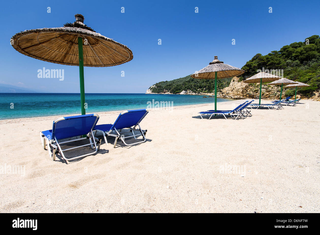 Sunbed and umbrella on the sunny beach. - Stock Image