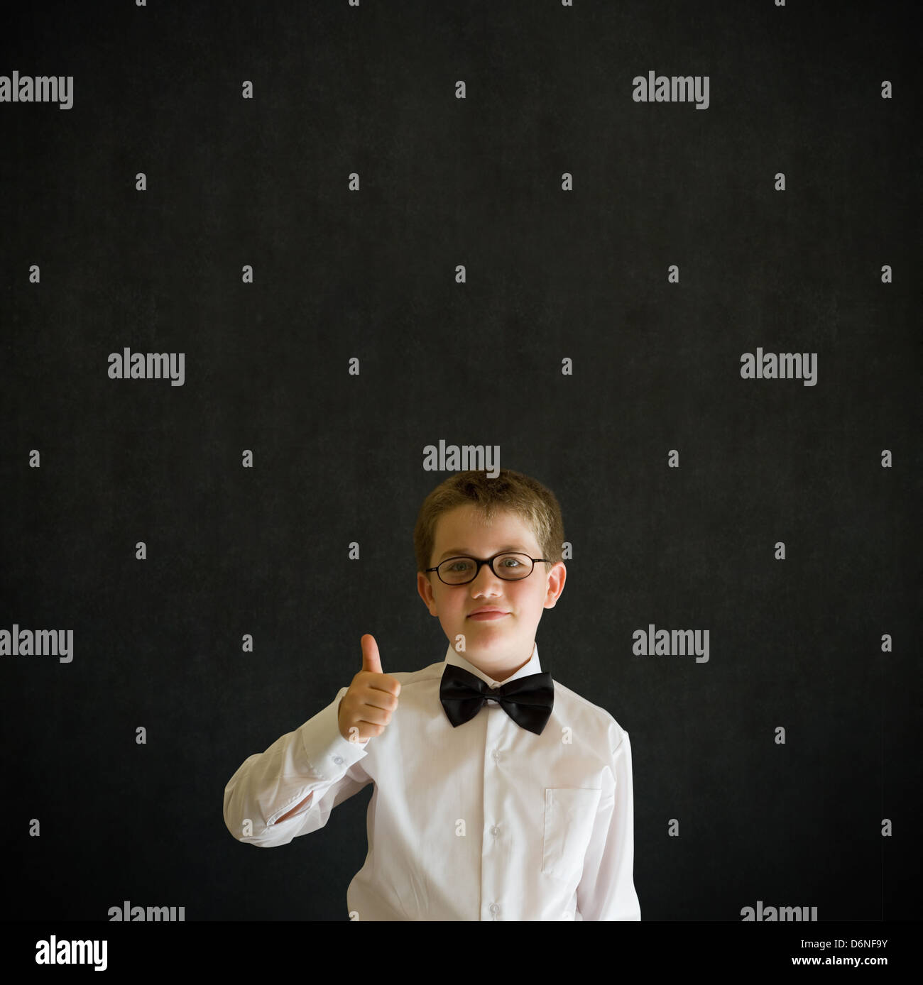 Thumbs up sign boy dressed up as business man, teacher or student on blackboard background Stock Photo