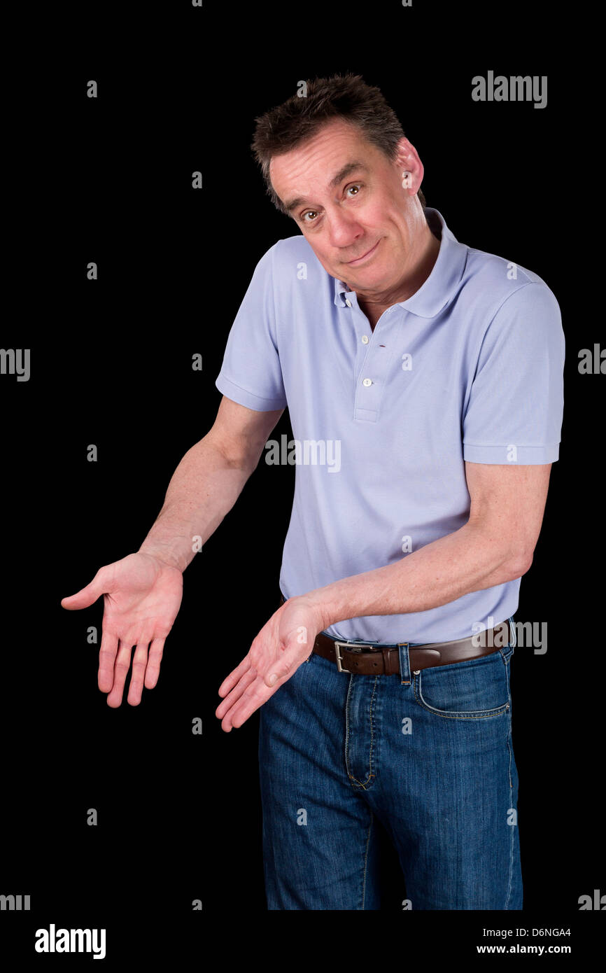 Smiling Middle Age Man Shrugging Hands Forward Pointing at Something Black Background - Stock Image