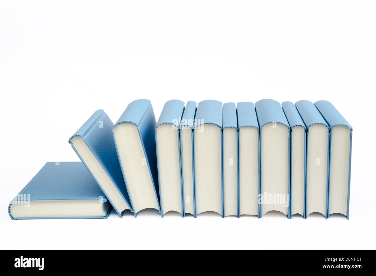 A group of blue books in a row on a white background - Stock Image