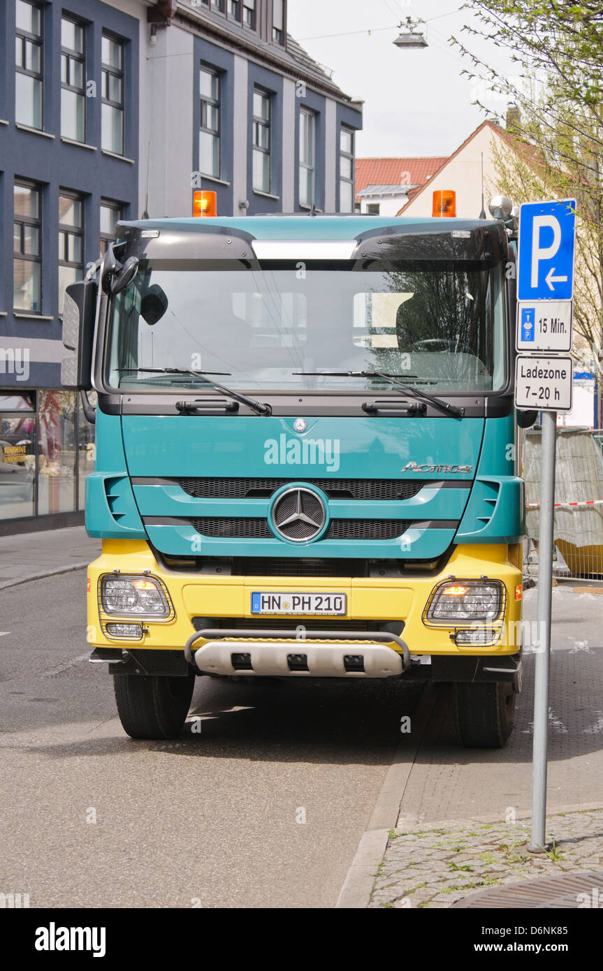 A green and yellow Mercedes Benz Actros truck parking in a parking place – Heilbronn, Germany - Stock Image
