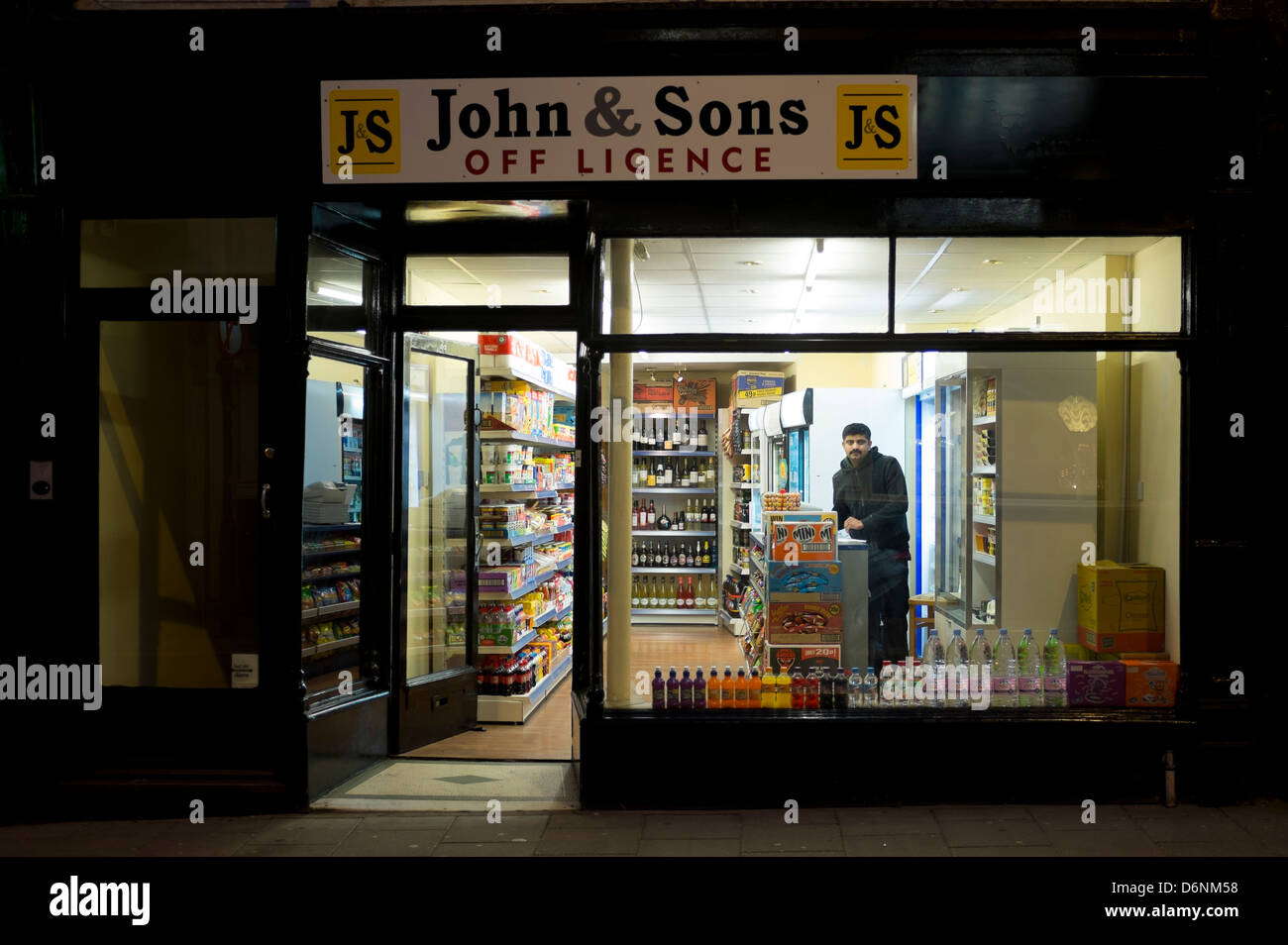 John and Sons, Off licence - a small independent retail convenience shop, exterior, night,  Aberystwyth Wales UK - Stock Image