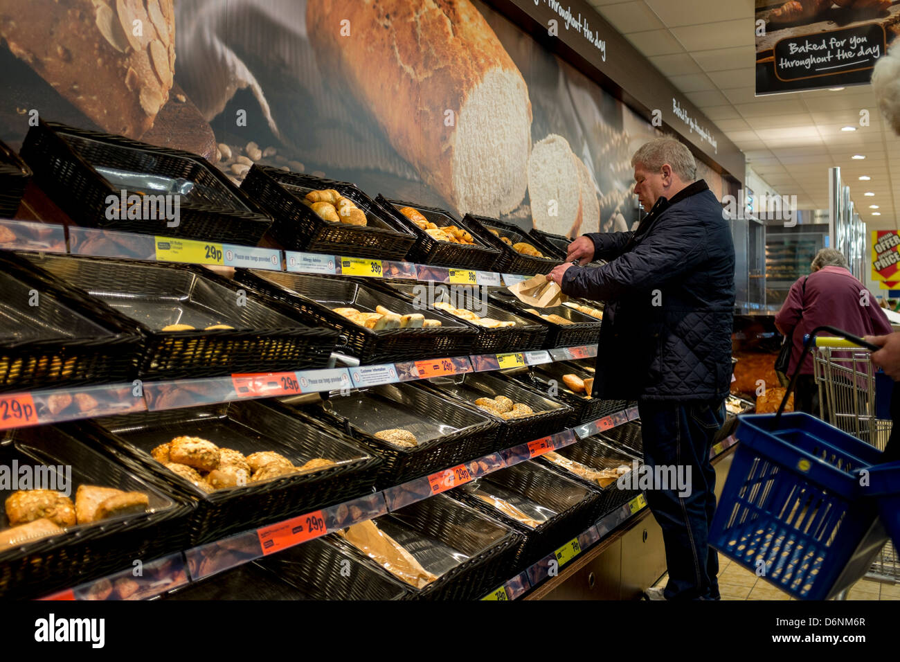 A man choosing freshly baked bread and other items from the bakery display at Lidls supermarket, Aberystwyth UK - Stock Image