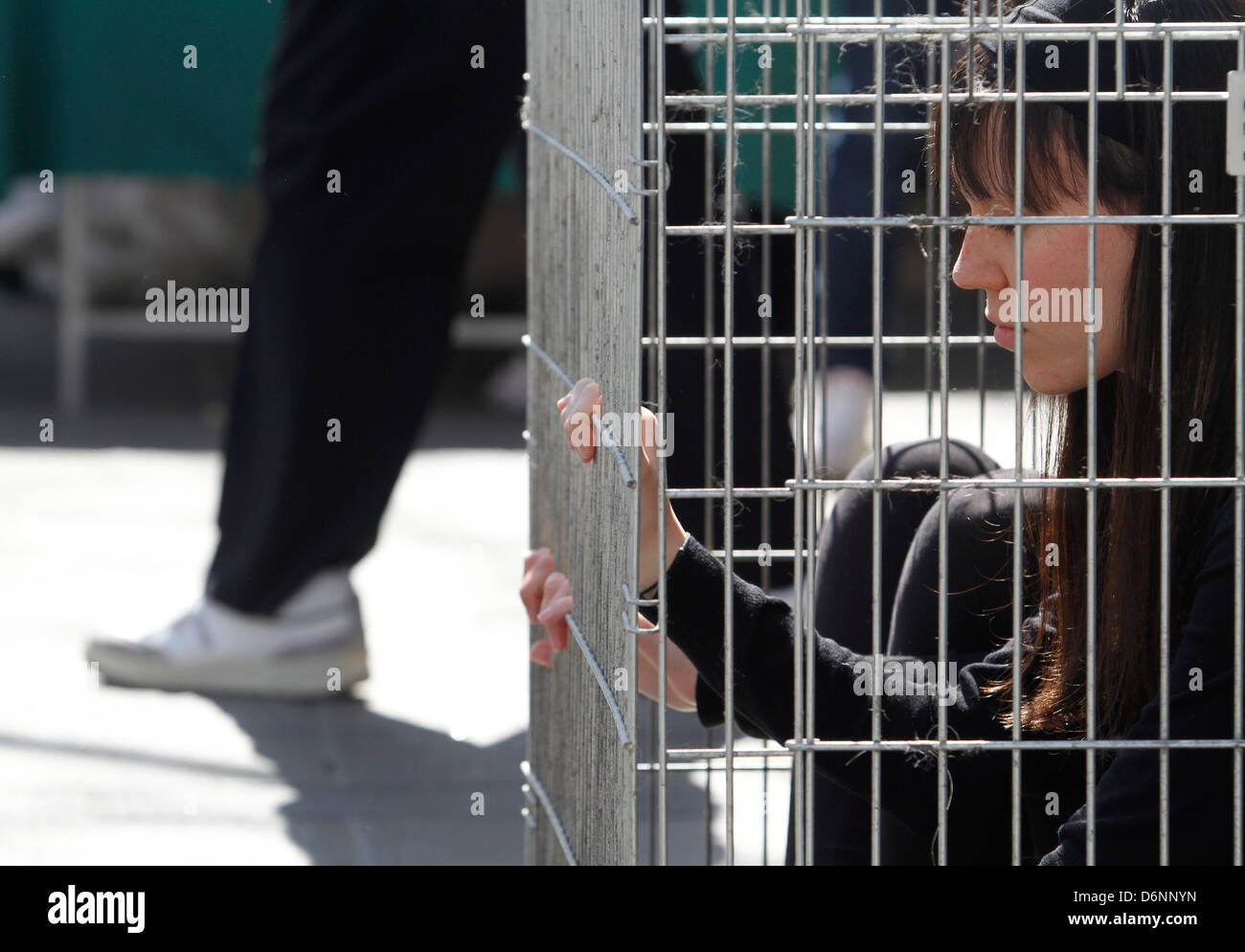 Activists enclosed in a cage are seen during a street performance - Stock Image