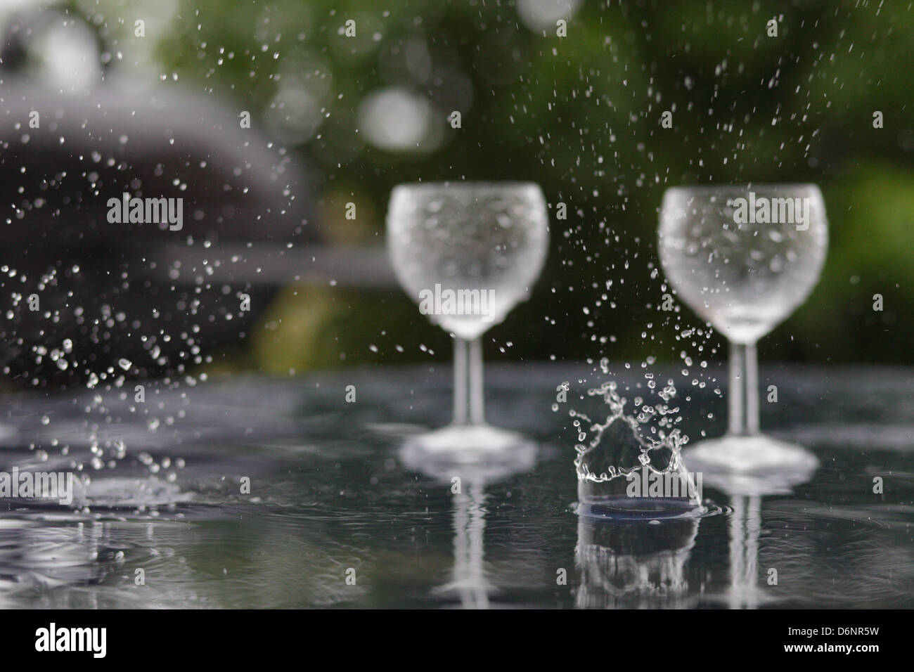 Le Barcares, France, forgotten in the rain wine glasses on a table - Stock Image