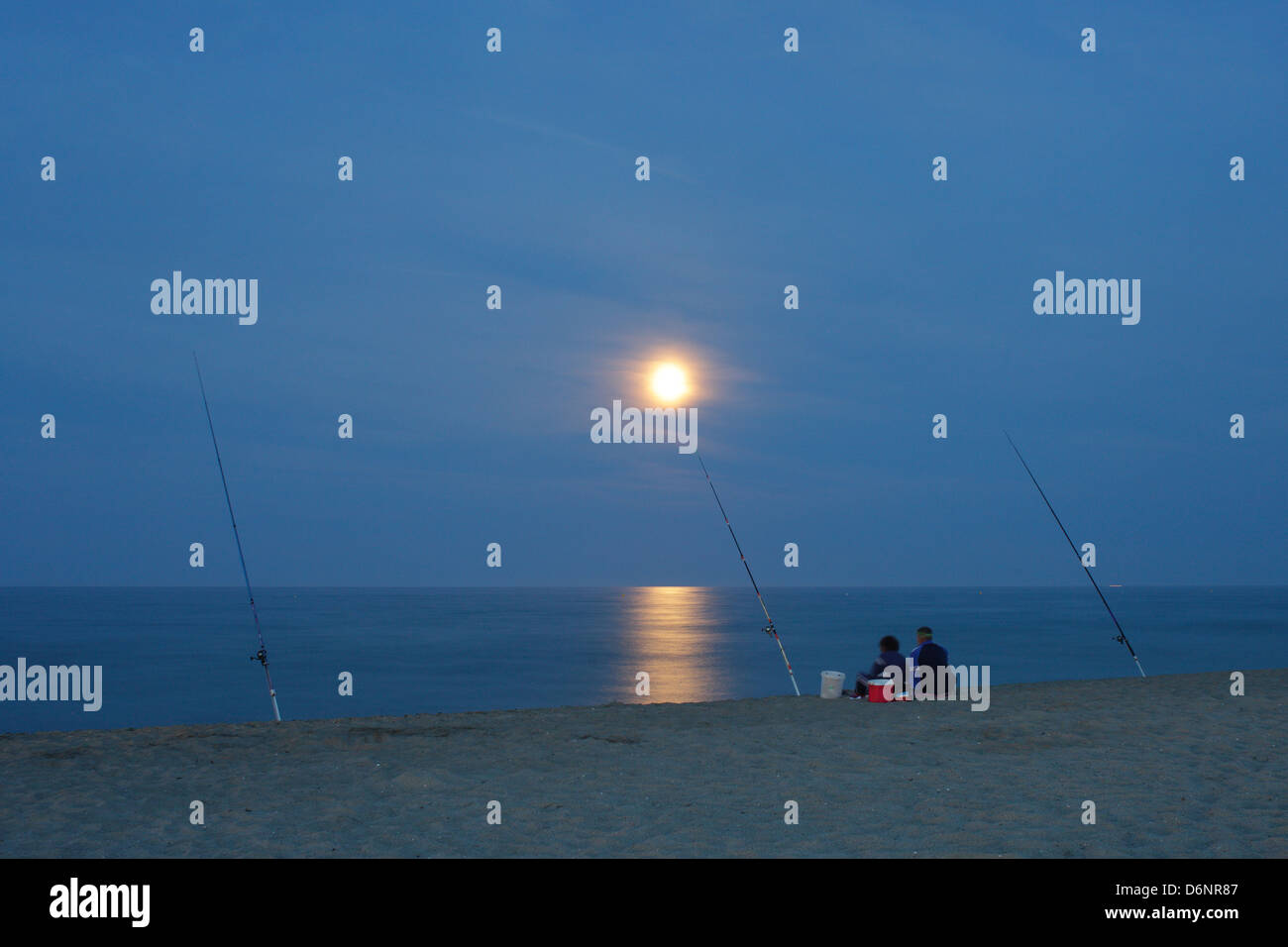 Le Barcares, France, two anglers at the full moon on the beach in the seaside resort of Le Barcares - Stock Image