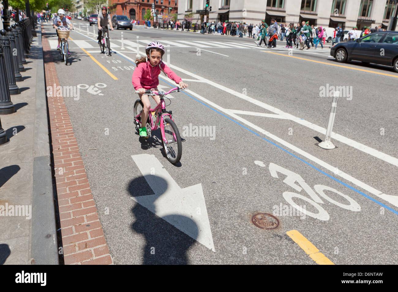 Small girl riding a bike in designated bicycle lane - Washington, DC USA - Stock Image