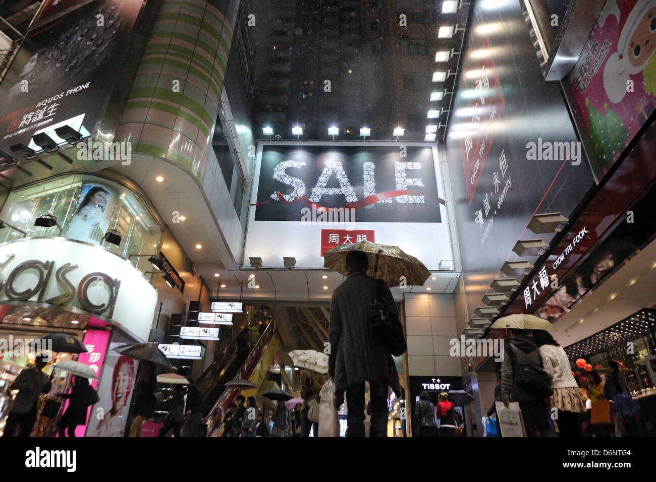 Hong Kong, China, people in rain in Causeway Bay district at night - Stock Image