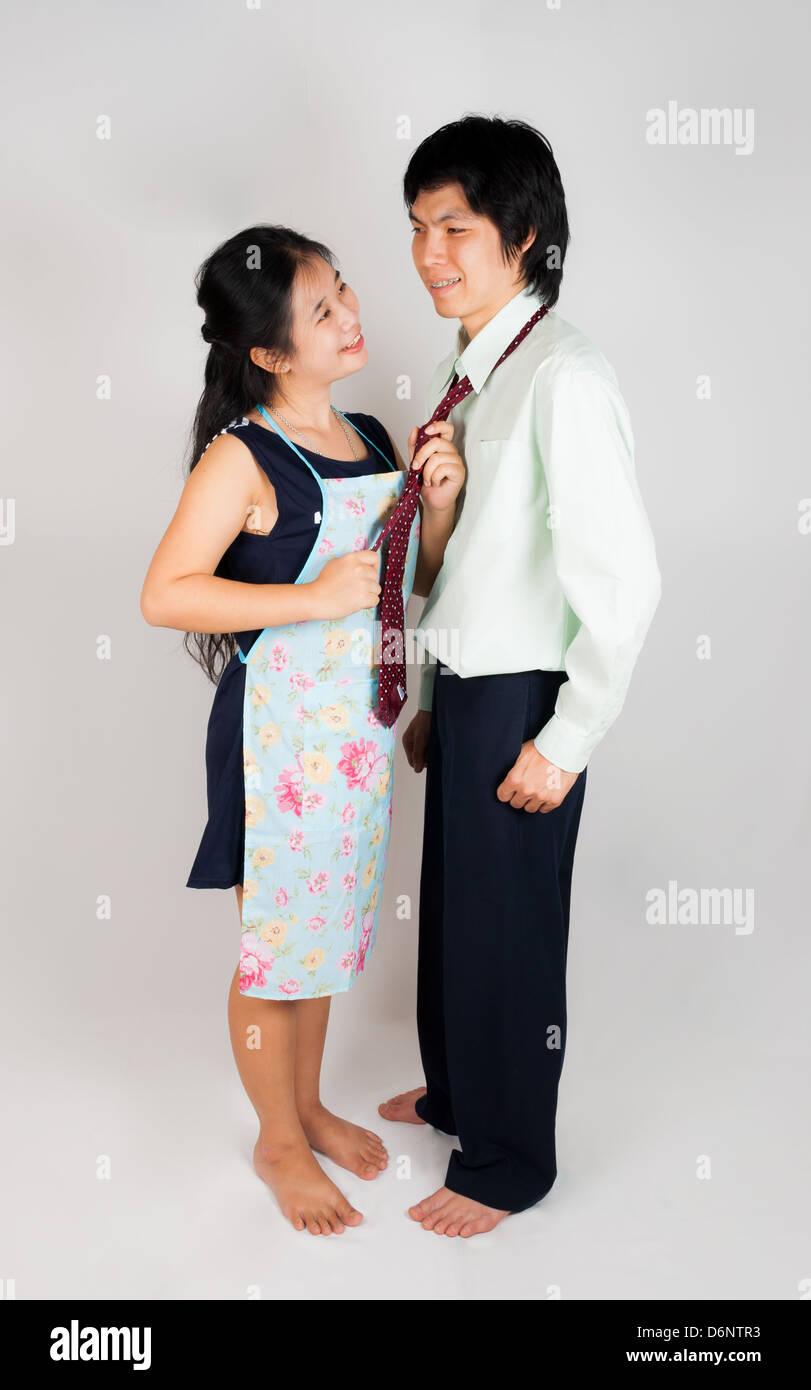 Wife ties husband's necktie with plenty of love - Stock Image