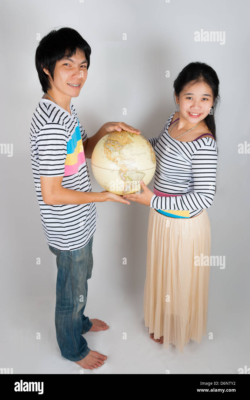 Asian Thai spouse hold Globe by their hands - Stock Image