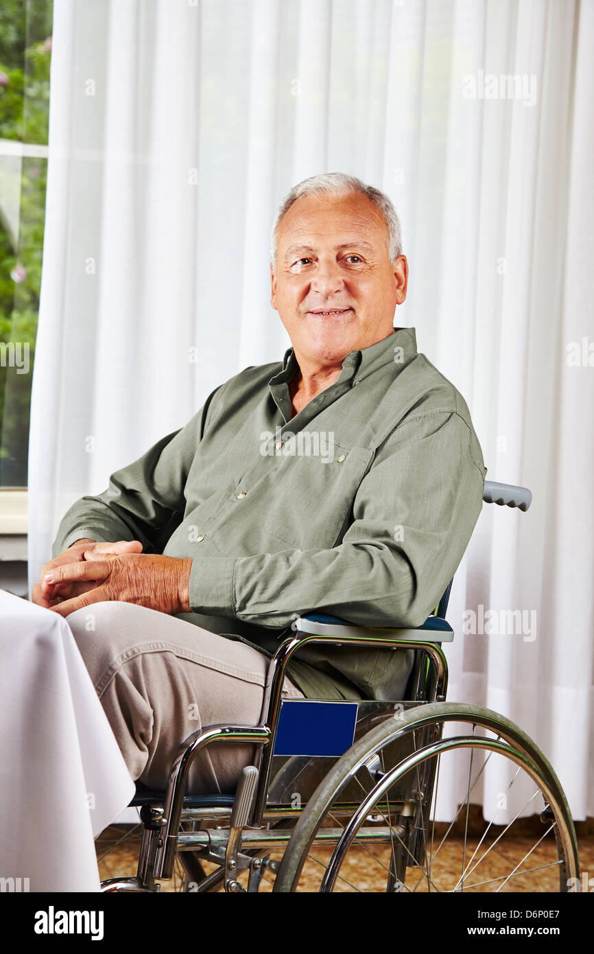 Smiling senior sitting in a wheelchair in a nursing home - Stock Image