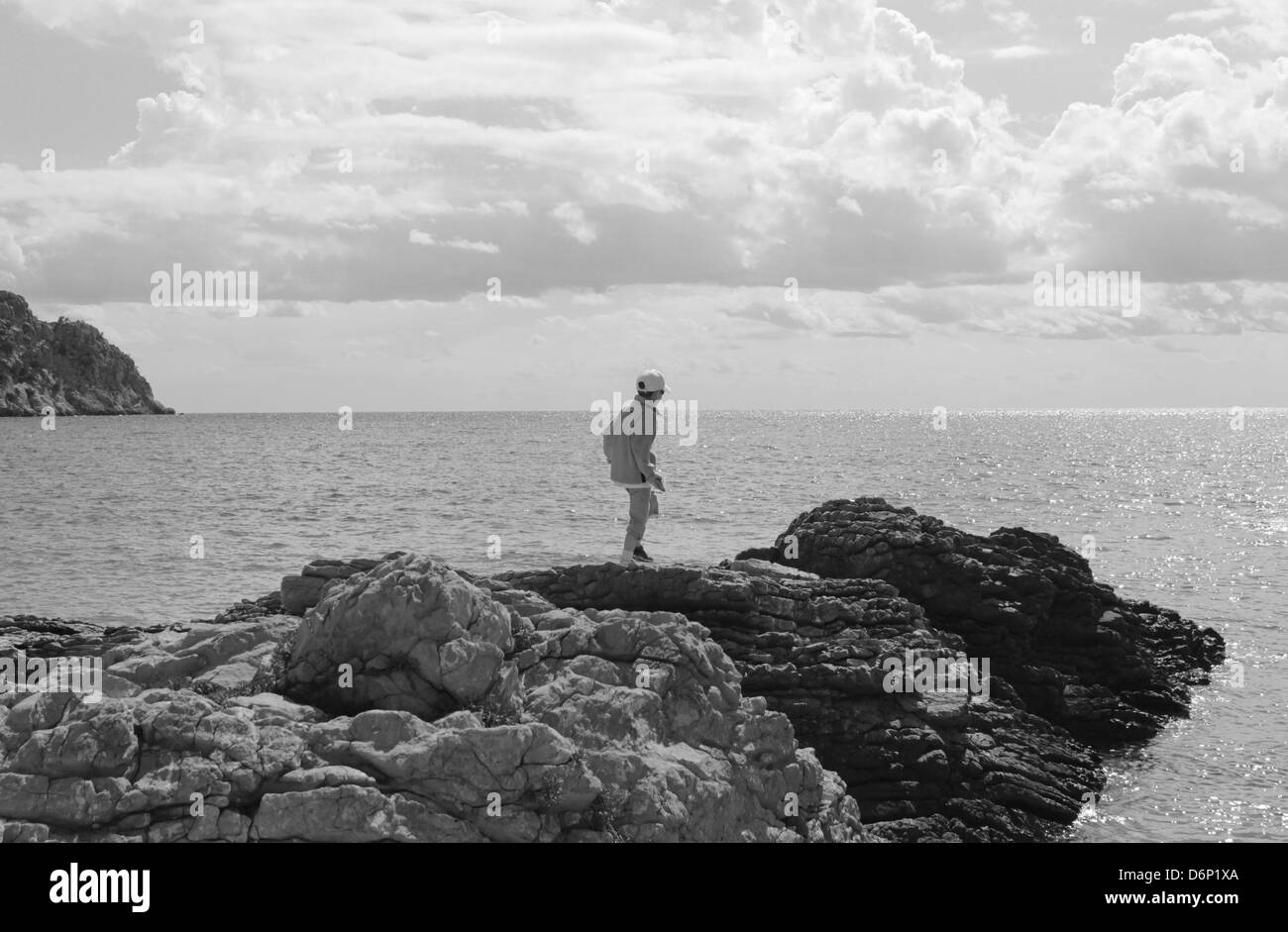 Boy exploring rocks by the sea - Stock Image