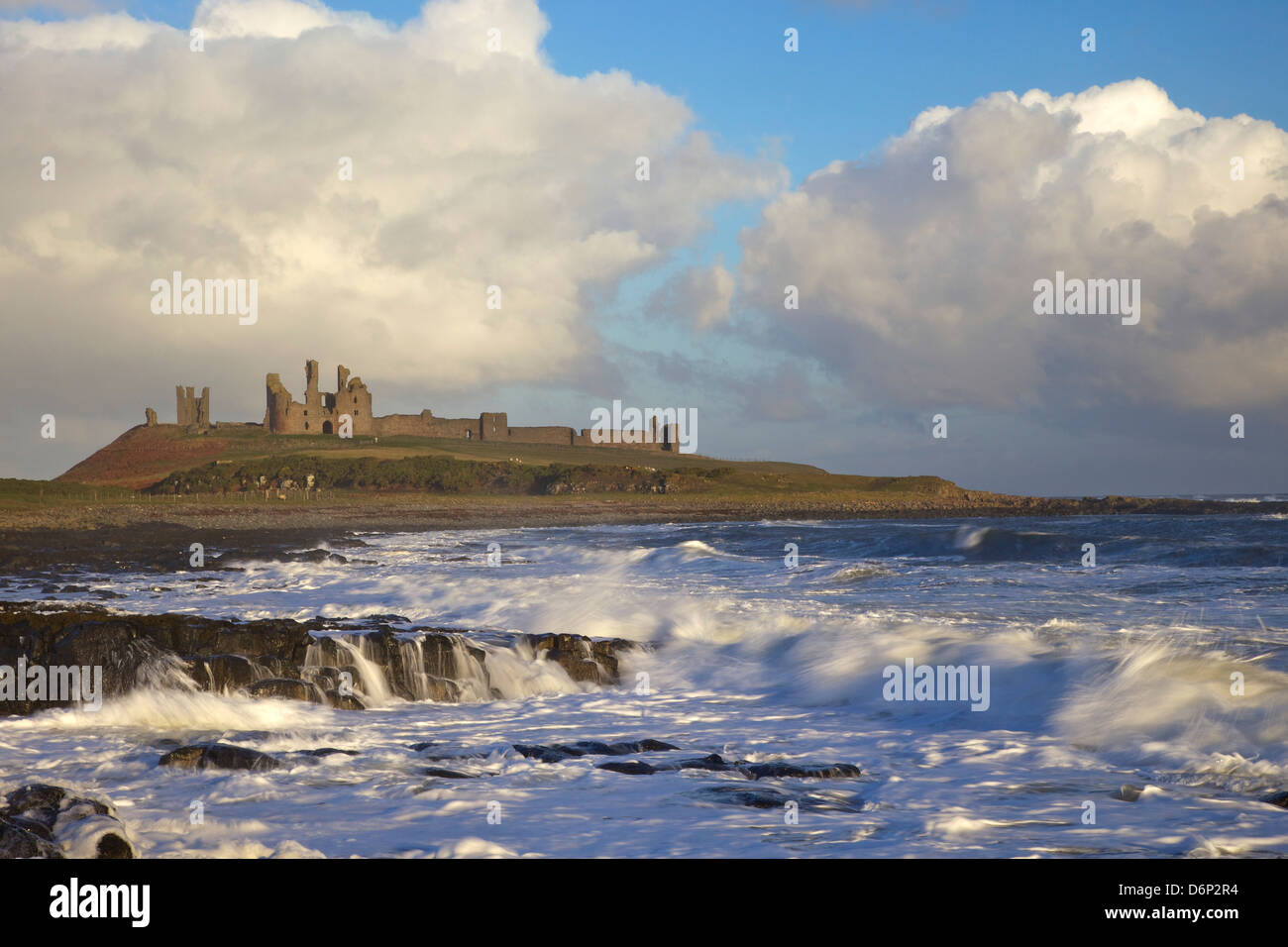 Surf on rocks, Dunstanburgh Castle, Northumberland, England, United Kingdom, Europe - Stock Image