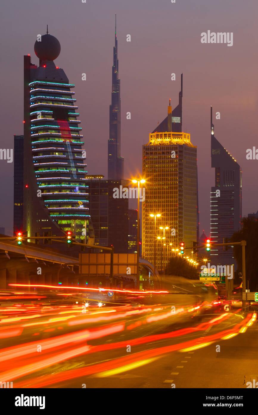 City skyline and car trail lights at sunset, Dubai, United Arab Emirates, Middle East - Stock Image