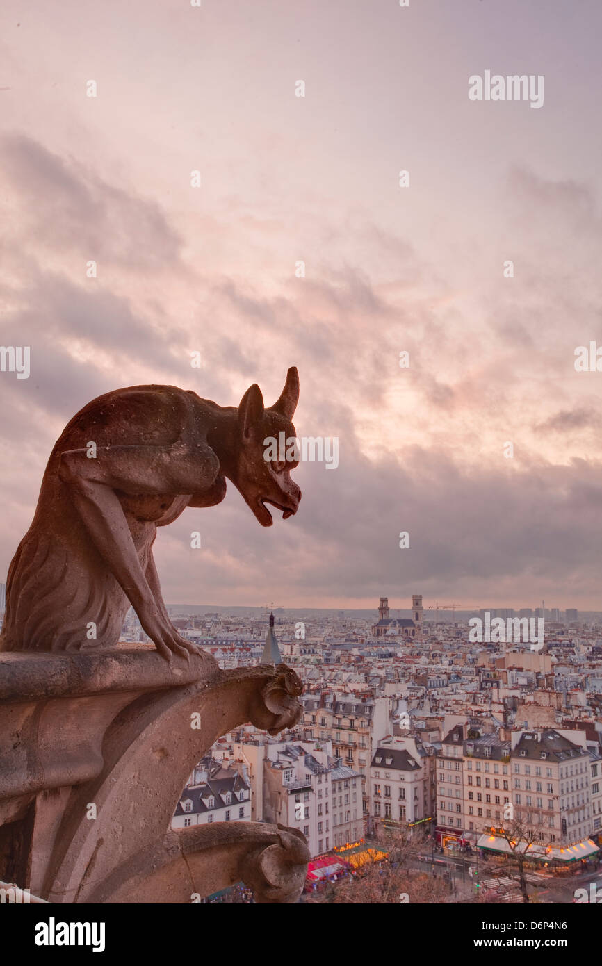 A gargoyle on Notre Dame de Paris cathedral looks over the city, Paris, France, Europe - Stock Image
