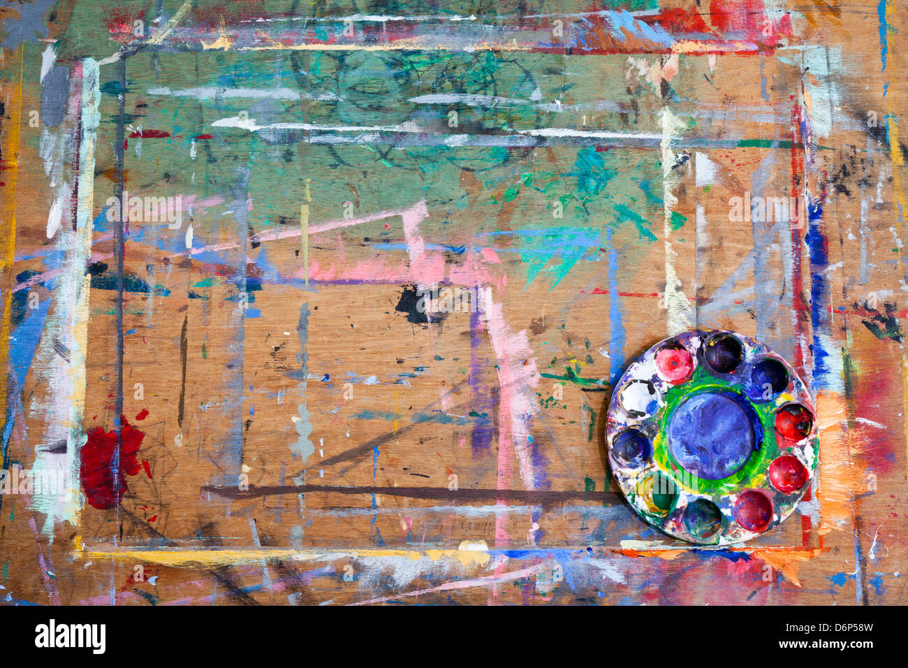 A paint splashed wooden board with a messy plastic paint palette in the bottom right corner. - Stock Image