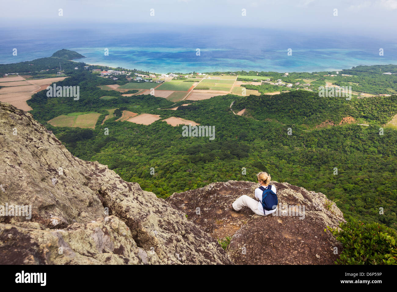 A woman sits and admires the coastal view from the top of Mount Nosoko in Ishigaki, Okinawa, Japan - Stock Image