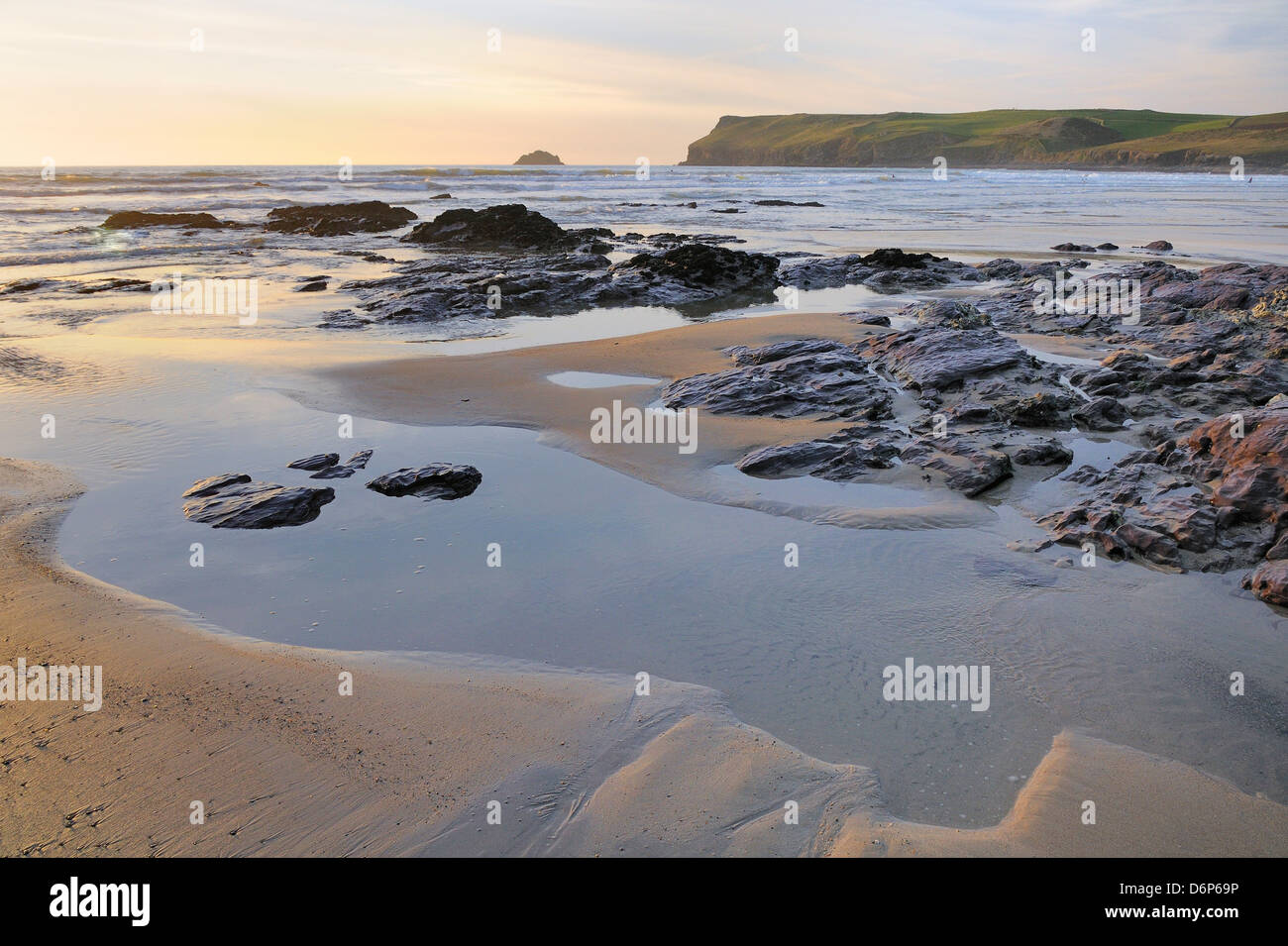 Tide retreating at sunset leaving tide pools among rocks, with Pentire Head in the background, Polzeath, Cornwall, - Stock Image