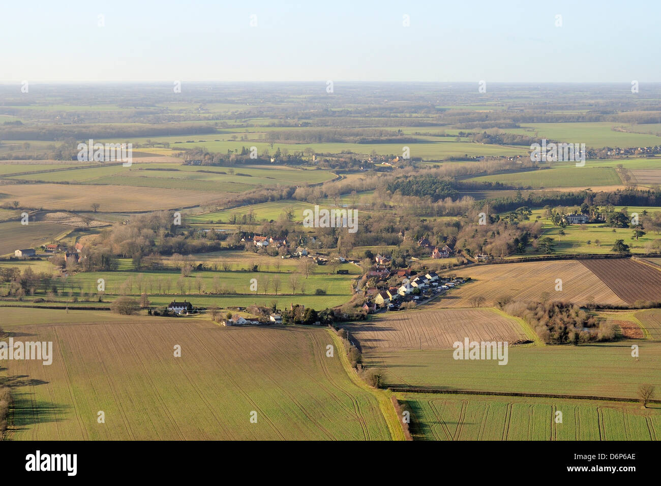 Aerial view of rolling rural landscape with small villages, winter wheat fields and pastureland, Suffolk, England, - Stock Image