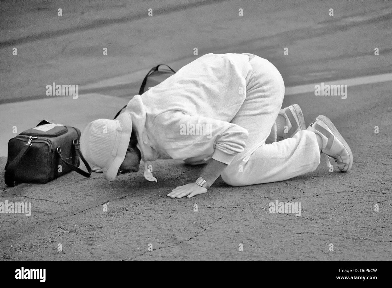 A Student from the Saint George's University School of Medicine in Grenada kisses the ground after arriving - Stock Image