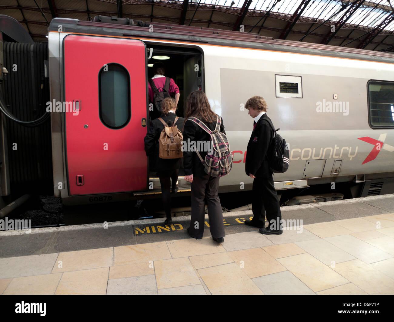 Schoolchildren in uniform boarding a train to commute home from school Bristol Temple Meads Railway Station England - Stock Image