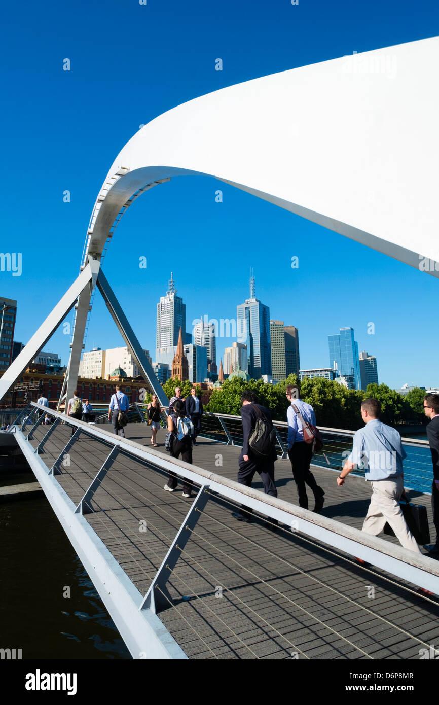 Pedestrians crossing Evan Walker Footbridge at Southbank  across Yarra River in central Melbourne Australia - Stock Image