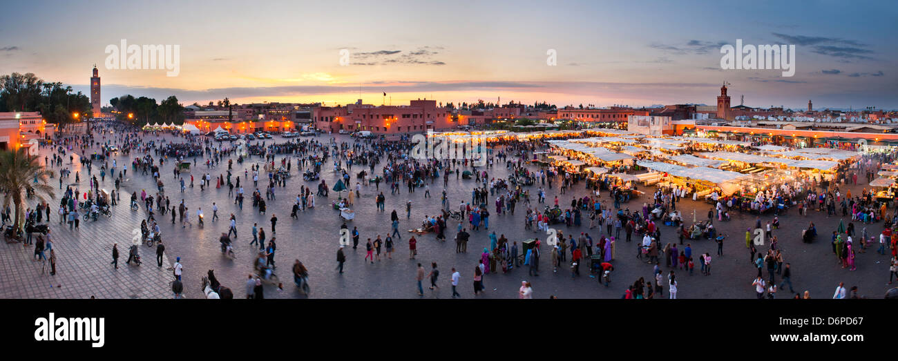 Food stalls, people and Koutoubia Mosque at sunset, Place Djemaa el Fna, Marrakech, Morocco, North Africa, Africa - Stock Image