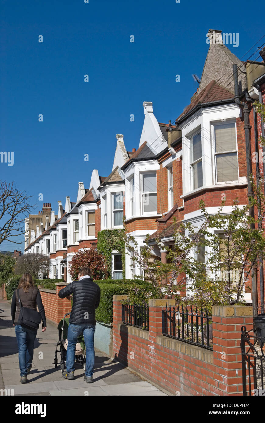 man and woman with baby buggy pass a row of 19th century houses with bay windows in wandsworth, southwest london, - Stock Image