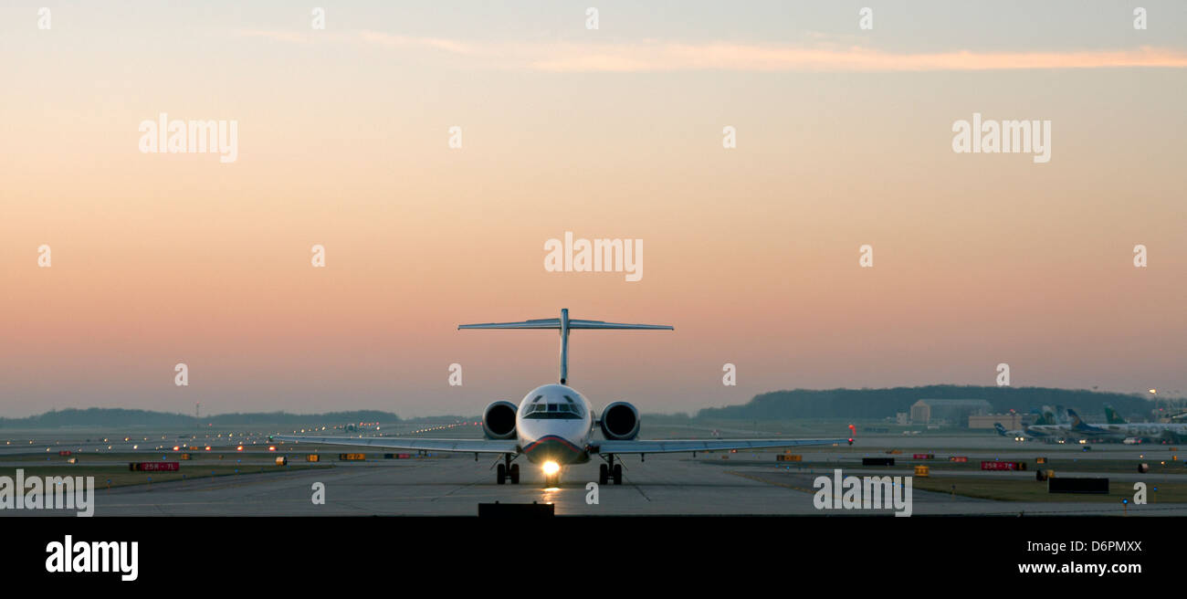 An airplane taxis down the runway before takeoff. - Stock Image