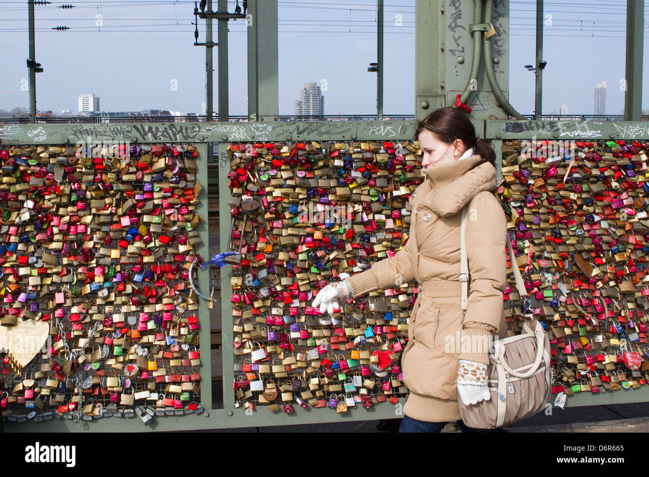 Woman walks past Ppdlocks on Cologne Railway Bridge signify ing couples' love for each other - Stock Image