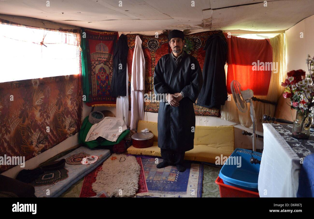 Gashijani stands on a carpet in his makeshift house in the Belvil settlement, which is inhabited by local Roma in - Stock Image