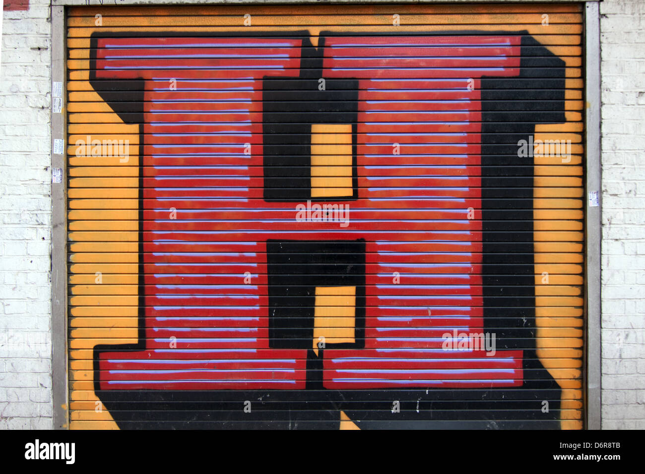 The letter H on a shutter in front of a shop  in London by the street artist Ben Eine - Stock Image