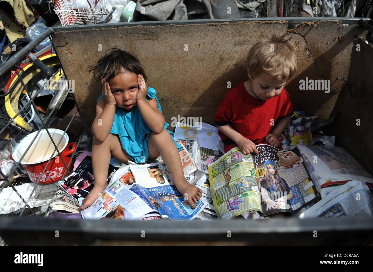 Children play between piles of rubbish in the Belvil settlement, which is inhabited by local Roma in Belgrade, Serbia, - Stock Image