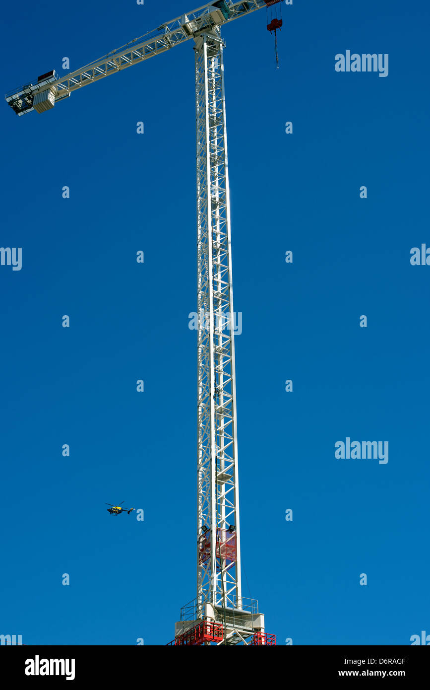 A crane towering above a London construction site set against a clear blue sky with a Police helicopter flying nearby - Stock Image