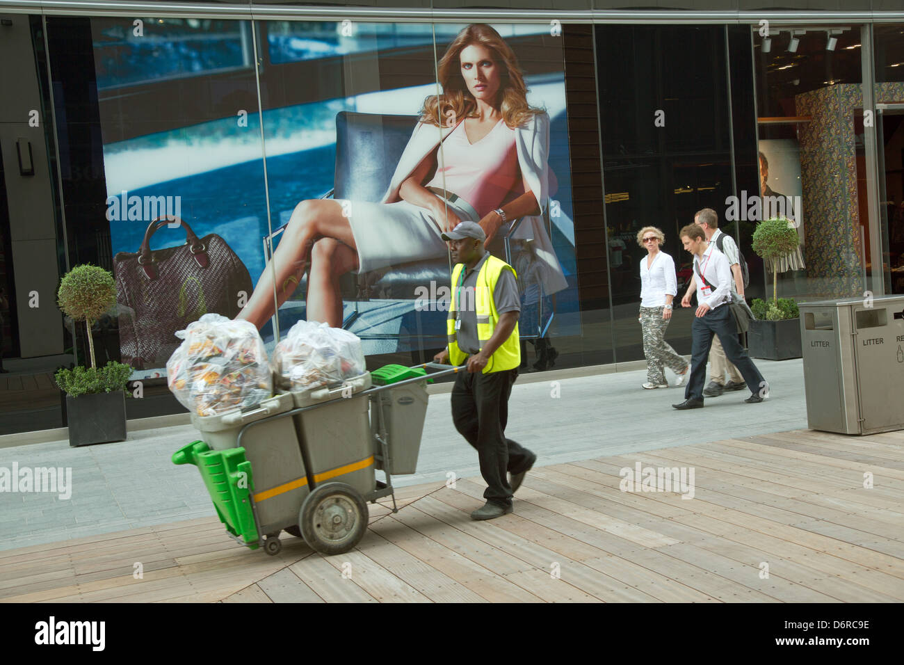 London, United Kingdom, Cleaner before the Boss Store (Hugo Boss) in the shopping mall Westfield Startford City - Stock Image