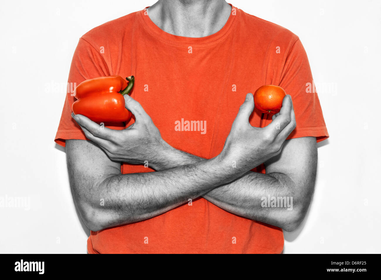 Midsection of man holding bell pepper and tangerine. Stock Photo
