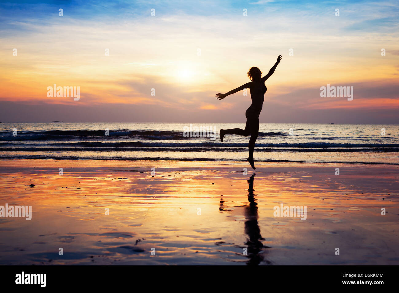 woman silhouette jumping on the beach at sunset - Stock Image