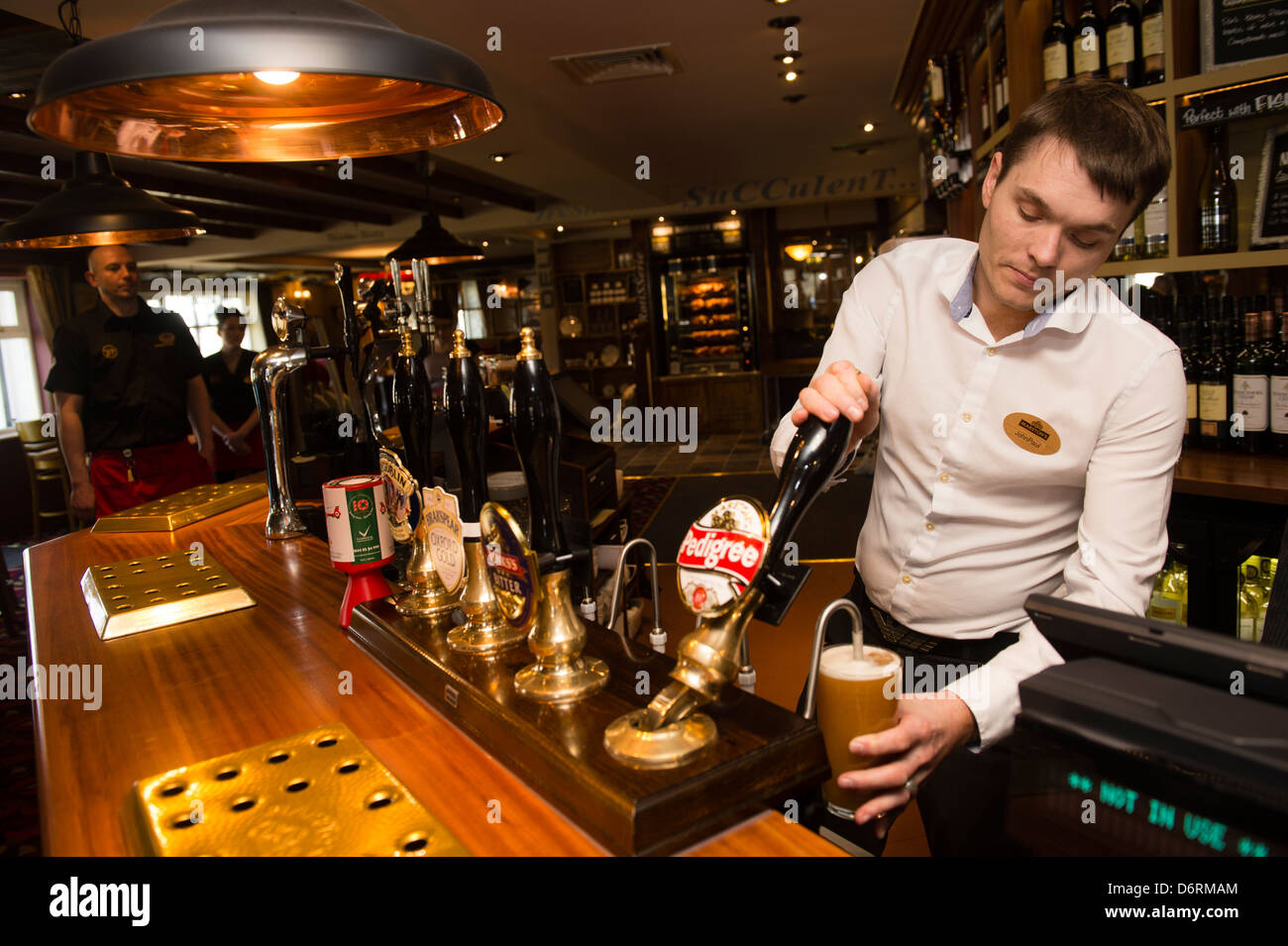 A barman pulling a pint of draught beer real ale, in a pub UK - Stock Image