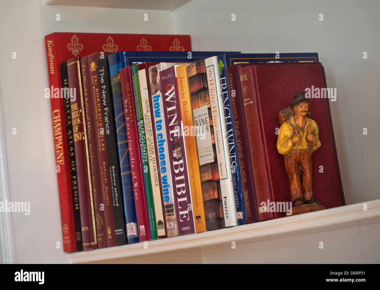 Variety of classic and contemporary wine reference books on bookshelf with grape harvester bookend figure - Stock Image