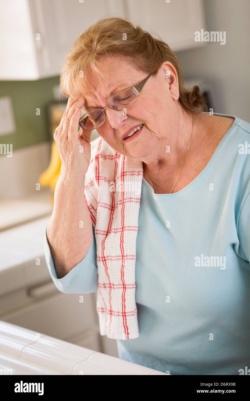 Grimacing Senior Adult Woman At Kitchen Sink With Head Ache. - Stock Image