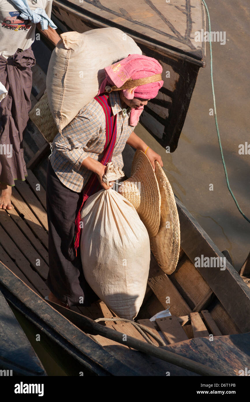 Woman carrying sacks off a boat, Inle Lake, near Indein and Nyaung Ohak villages, Shan State, Myanmar, (Burma) - Stock Image