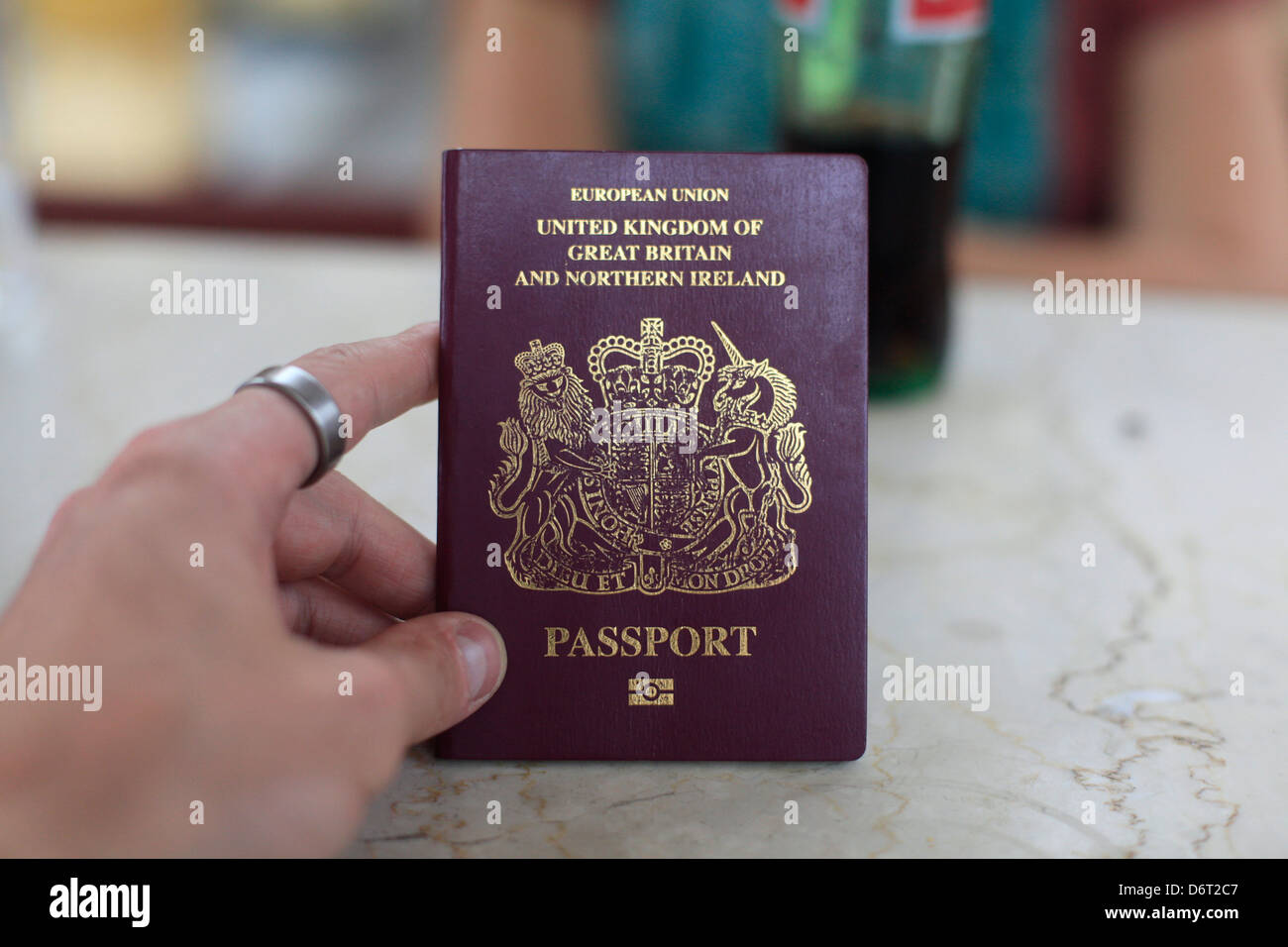 A UK passport is held by a tourist traveling in India - Stock Image