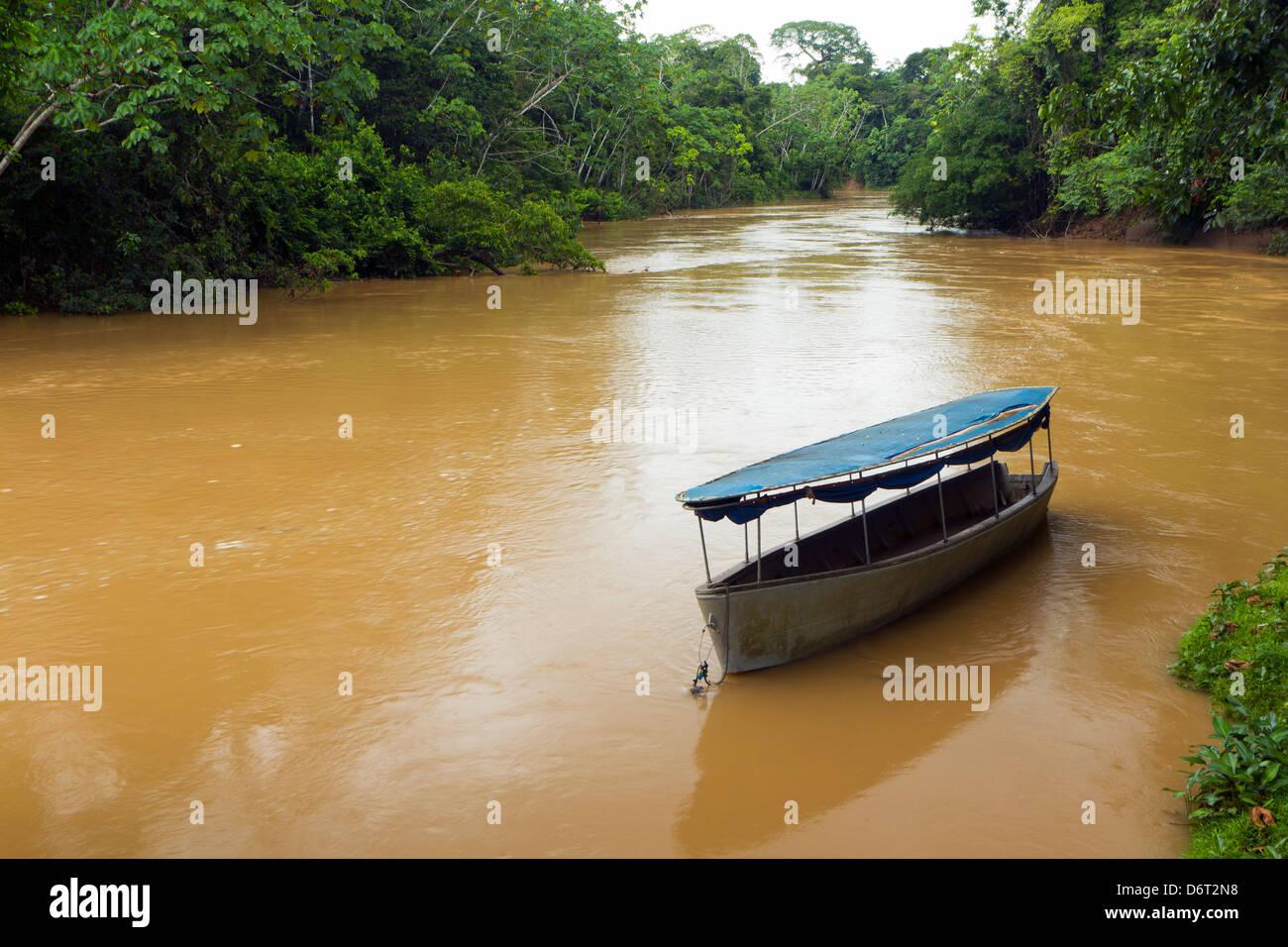 Canoe moored beside the Rio Tiputini in the Ecuadorian Amazon - Stock Image