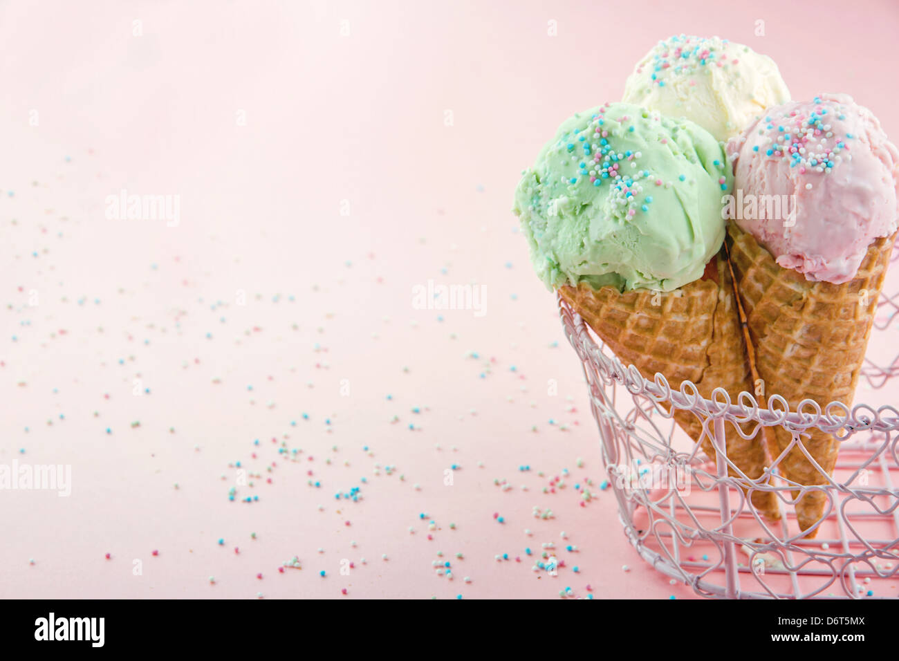 Ice cream cones in an metal basket in pink shabby chic vintage background - Stock Image
